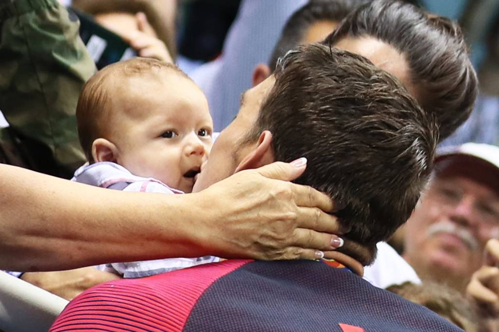 O nadador americano Michael Phelps beija seu filho Boomer, após conquistar medalha de ouro nos 200m nado borboleta, no Parque Aquático Olímpico, no Rio de Janeiro (RJ) - 09/08/2016