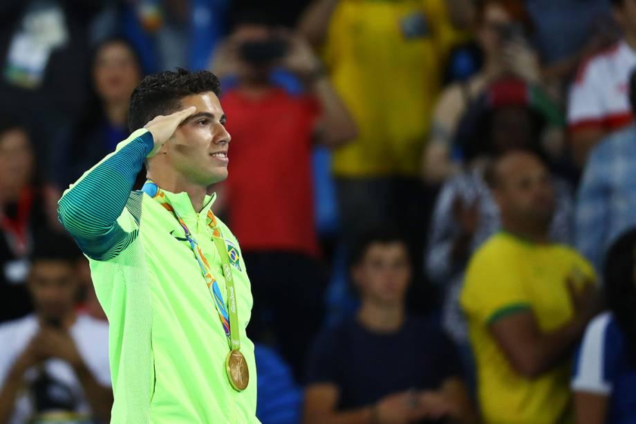 O brasileiro Thiago Braz presta continência no pódio, após conquistar a medalha de ouro no salto com vara, nos Jogos Olímpicos Rio 2016