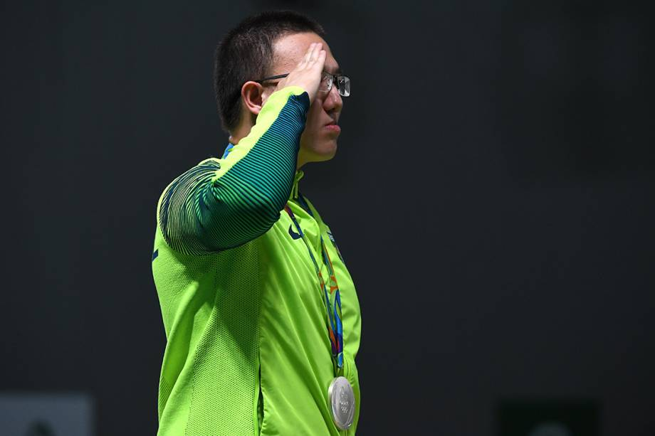 O brasileiro Felipe Wu presta continência no pódio, após levar a medalha de prata nos 10m tiro com pistola
