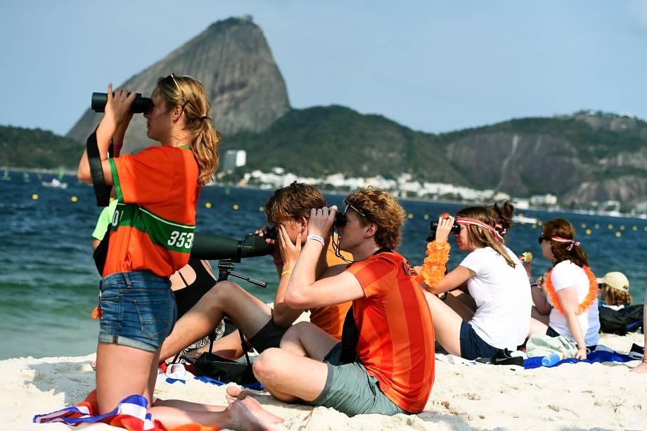 Torcedores usam binóculos para acompanhar a prova de vela na Baía de Guanabara nos Jogos Olímpicos Rio 2016