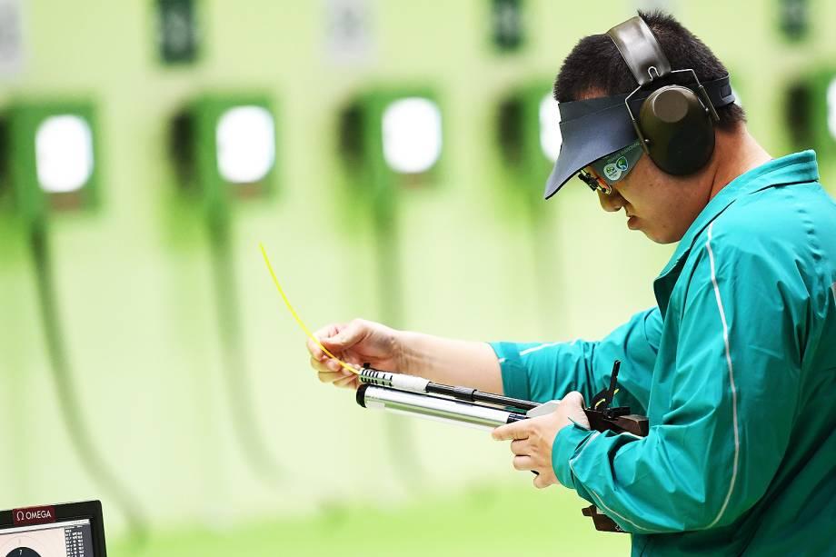 Felipe Wu limpa sua pistola durante competição nos 10m tiro com pistola, no Rio