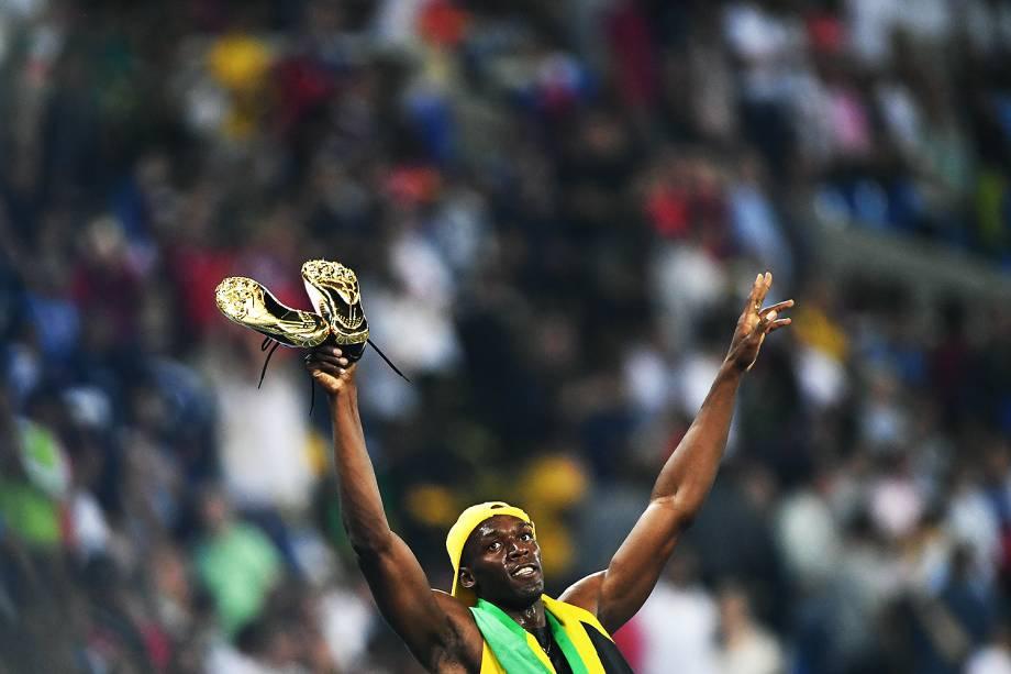 Usain Bolt comemora com as sapatilhas douradas a conquista do tri olímpico nos 100m rasos