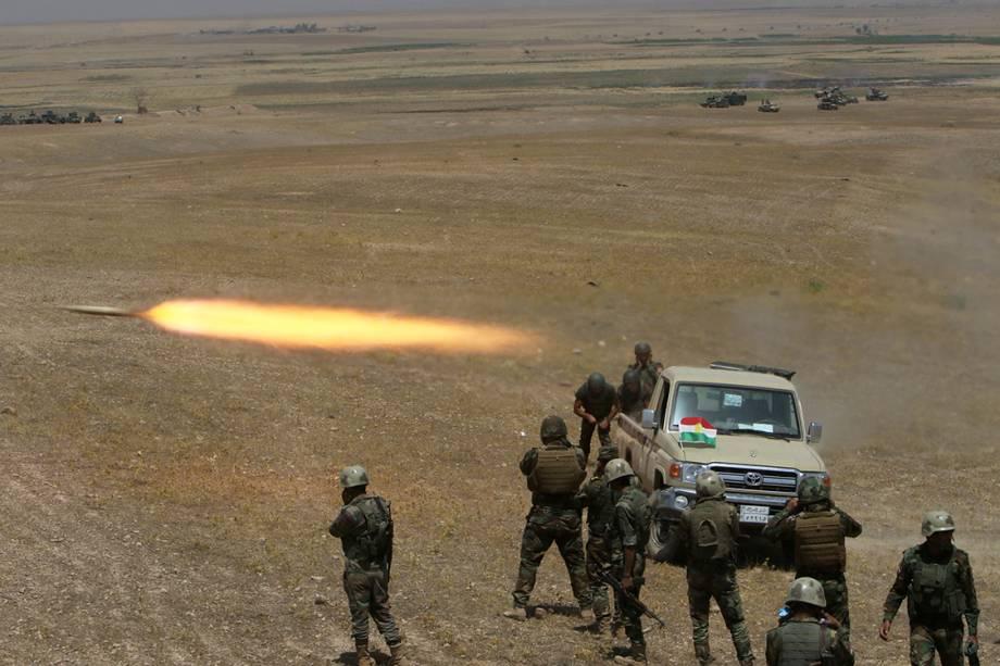 Soldados das forçcas curdas peshmerga lançam um foguete contra militantes do Estado Islâmico, próximo a Mosul , no Iraque