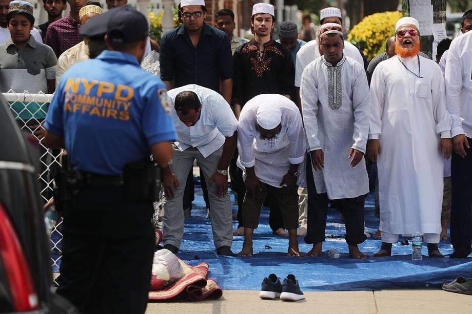 Homens rezam em frente a mesquita Al-Furqan Jame Masjid, onde dois muçulmanos foram assassinados, no bairro do Queens, em Nova York