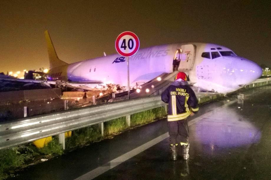 Bombeiro fotografado em frente a um avião de carga que saiu da pista após o pouso e deslizou para uma estrada local em Orio al Serio, perto de Milão, na Itália - 05/08/2016