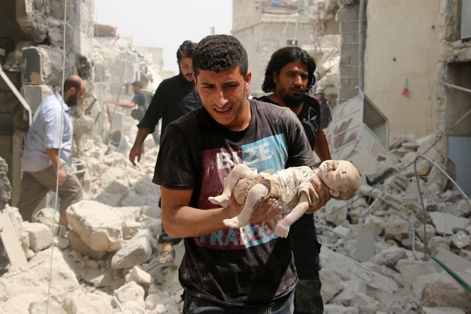 Morador sírio carrega um bebê morto retirado dos escombros de edifícios depois de um ataque a bomba no bairro de Bab al-Nairab na cidade síria do norte de Aleppo – 25/08/2016