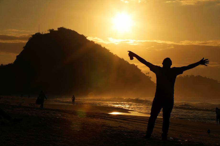 Homem acompanha amanhecer do Sol na Praia de Copacabana, no Rio de Janeiro (RJ) - 23/08/2016