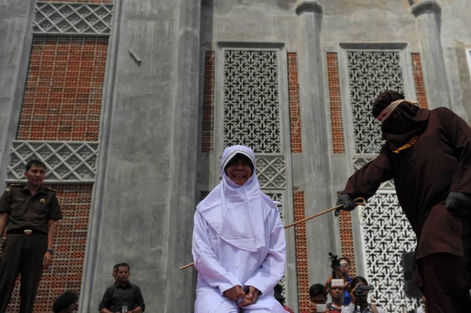Mulher é castigada com golpes de bastão como punição por encontrar um homem sem estar casada com ele, atitude condenada pela lei islâmica da Sharia, em frente a uma mesquita em Banda Aceh, na Indonésia - 01/08/2016