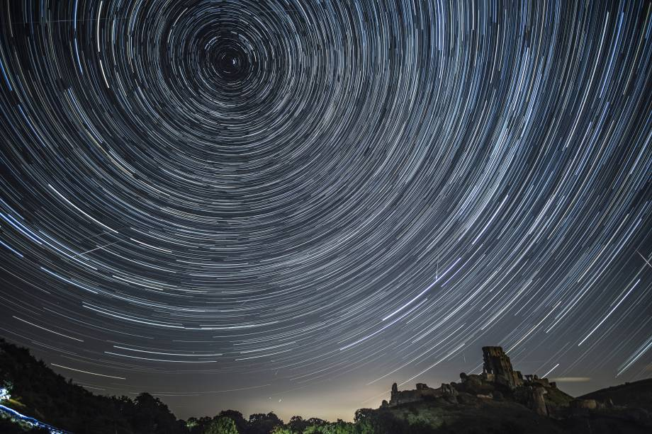 Satélites, aviões e cometas em trânsito riscam o céu sob as estrelas em Corfe Castle, no Reino Unido - 12/08/2016