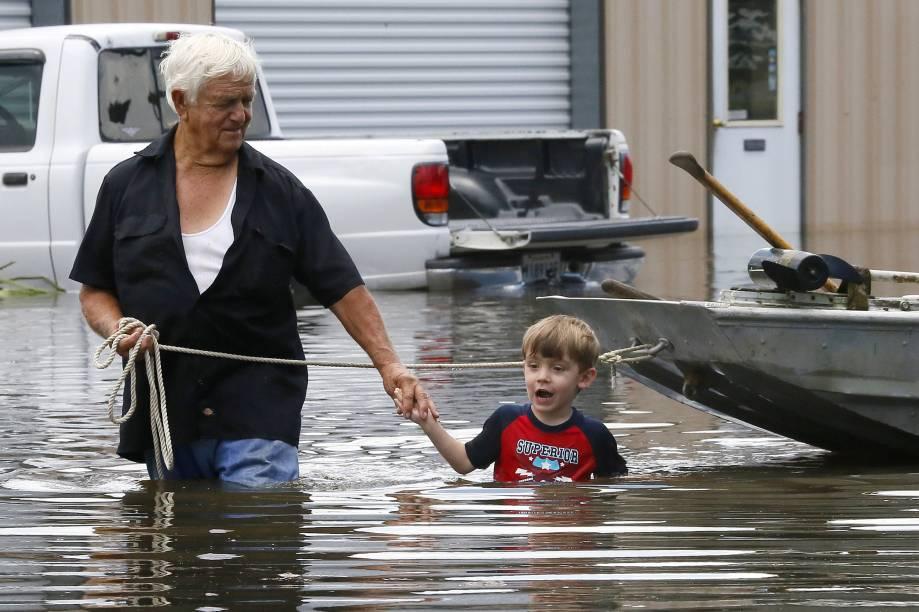 Senhor e seu neto caminham por uma área alagada em St. Amant, em Louisiana, após fortes tempestades atingirem a região, nos Estados Unidos - 15/08/2016