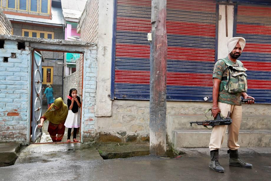 Garota observa soldado em uma rua de Srinagar, na Caxemira. A cidade permanece sob toque de recolher após semanas de intensos conflitos na região - 19/08/2016