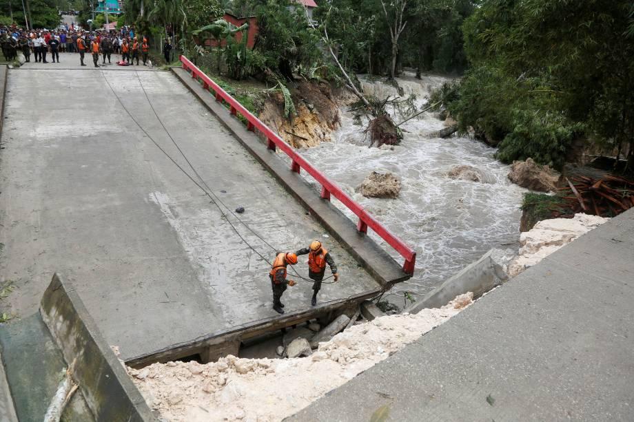 Os membros da comissão de emergência da Guatemala trabalham em uma ponte que desabou após as fortes chuvas provocadas pelo furacão Earl na cidade de Menchor de Mencos - 04/08/2016