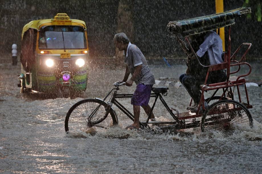 Homem transporta passageiros em sua bicicleta em meio a uma rua inundada em Nova Délhi, na Índia - 31/08/2016