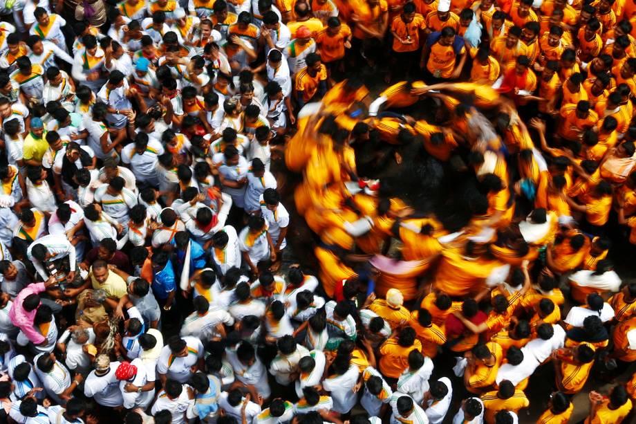 Devotos dançam em círculos após quebrarem uma panela de barro contendo coalhada, durante o Festival Janmashtami, em Mumbai, na Índia - 25/08/2016