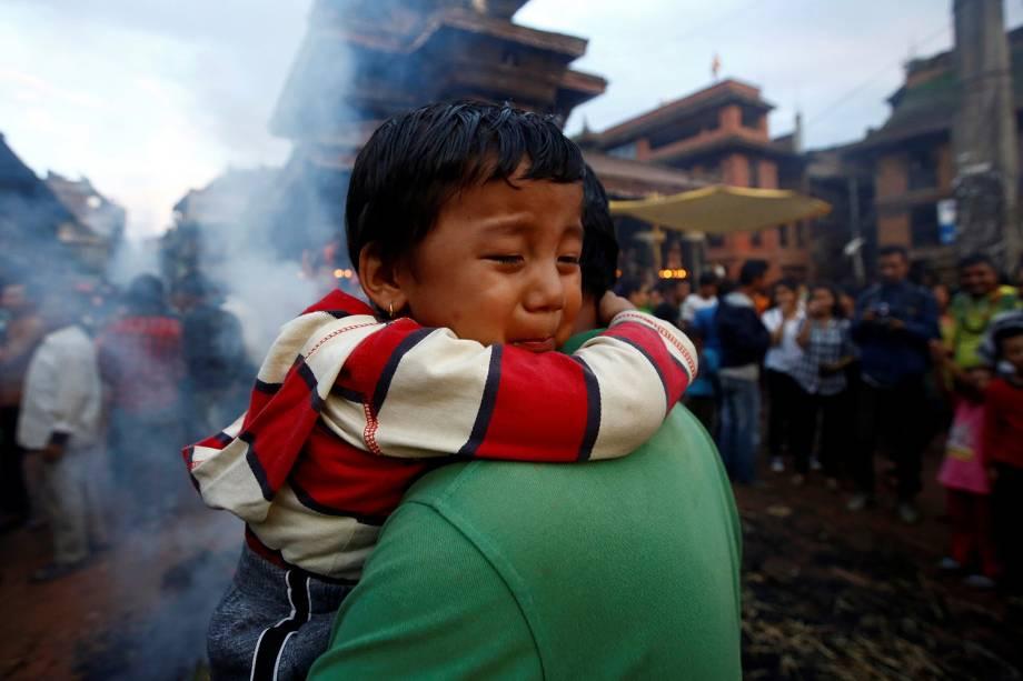 Criança abraça a mãe, enquanto pessoas colocam fogo em uma efígie que representa o demônio Ghantakarna para simbolizar a destruição do mal durante um festival na cidade de Bhaktapur, no Nepal