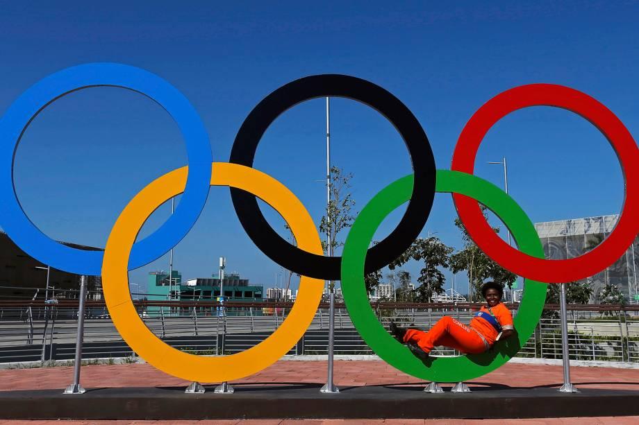 Funcionária do serviço de limpeza urbana tira foto nos anéis olímpicos instalados no Parque Olímpico, no Rio de Janeiro - 01/08/2016