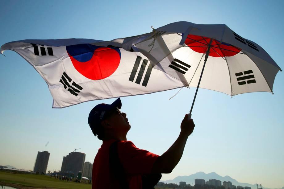Torcedor estende bandeira sul-coreana e abre um guarda-chuva, durante a competição do golfe feminino na Rio-2016 - 17/08/2016