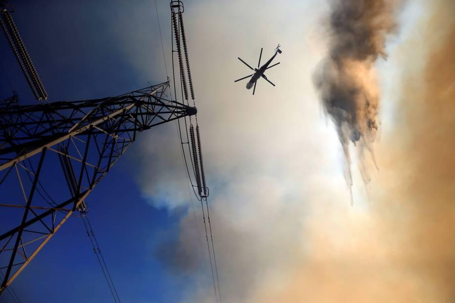Helicóptero de combate a incêndios faz operação próximo a linhas de de transmissão para proteger casas durante incêndio no Condado de San Bernardino, na Califórnia (EUA) - 17/08/2016
