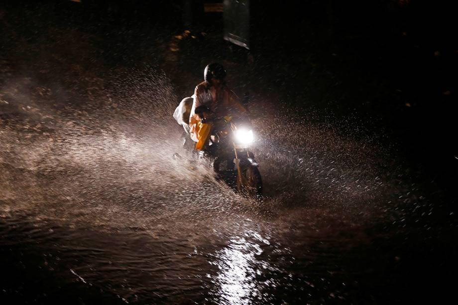 Motociclista passa por área alagada depois de fortes tempestades atingirem a região de Nova Délhi, na Índia - 01/08/2016