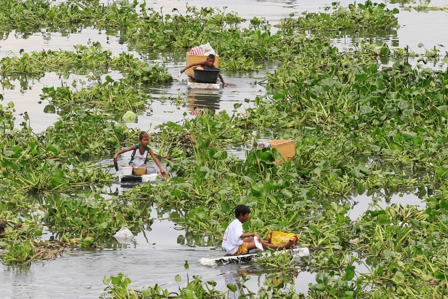 Meninos percorrem um rio poluído usando jangadas improvisadas de isopor para coletar itens reutilizáveis em Manila, nas Filipinas - 01/08/2016