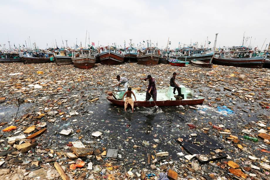 Garotos a bordo de um barco abandonado coletam materiais recicláveis, próximos a barcos de pesca no porto de Karachi, no Paquistão - 17/08/2016