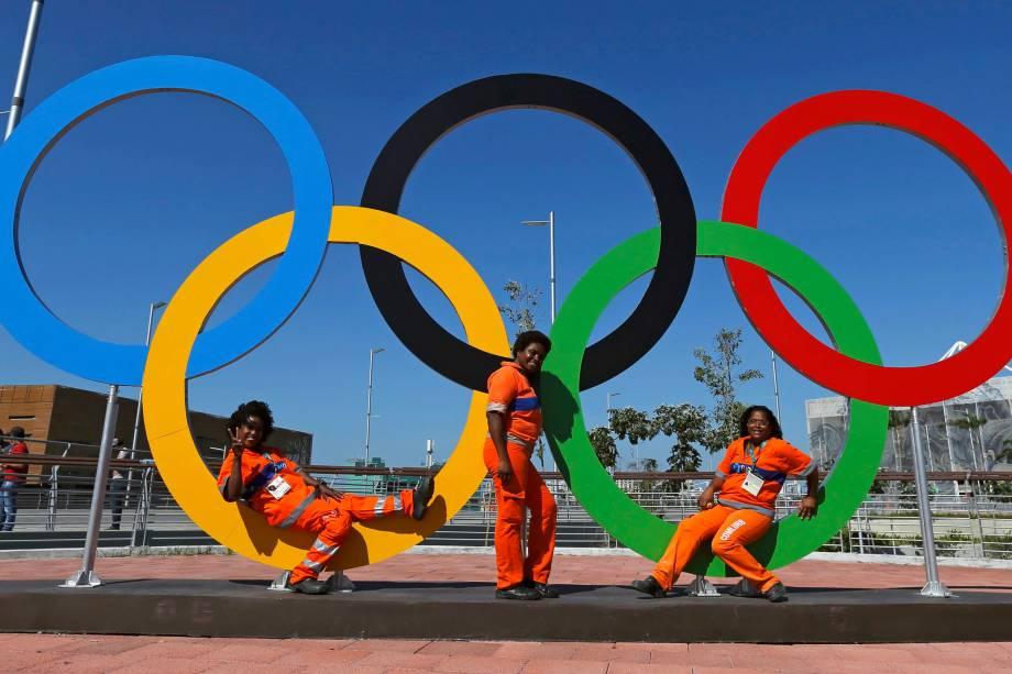 Funcionárias posam em frente aos anéis, símbolos da Olimpíada, no Parque Olímpico do Rio de Janeiro - 01/08/2016