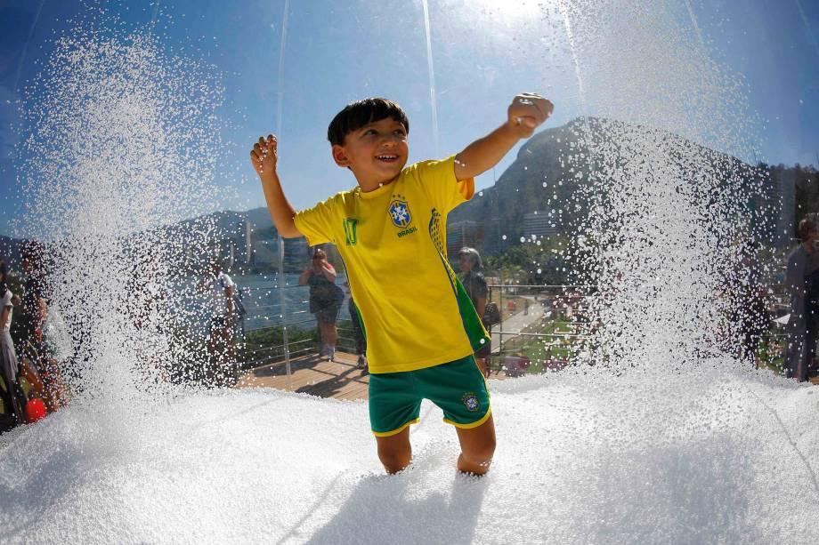 Garoto brinca em uma fonte em frente às instalações da Suiça, na Vila Olímpica - 01/08/2016