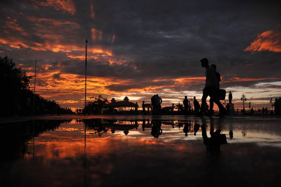 Pedestres caminham durante o pôr do sol depois de uma chuva torrencial na cidade de Shimla, norte da Índia - 18/08/2016