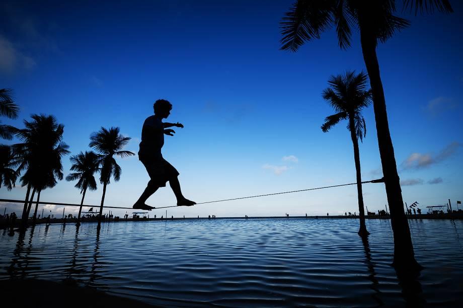 Um homem caminha em um slackline entre duas palmeiras na praia de Copacabana, no Rio de Janeiro. A cidade está fazendo os últimos  preparativos para os Jogos Olímpicos Rio 2016