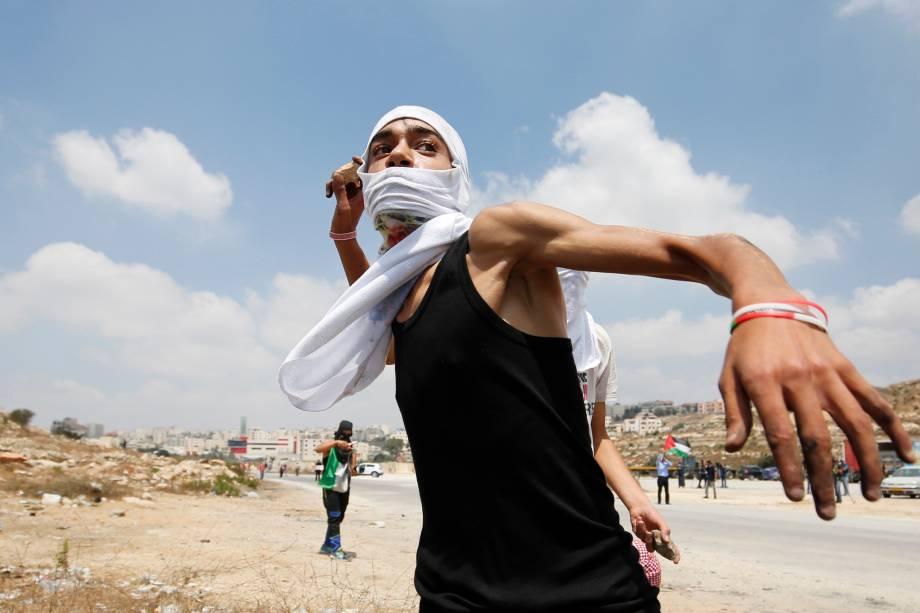 Palestino atira pedras em direção as forças de segurança israelenses durante confrontos na sequência de uma manifestação em solidariedade aos prisioneiros palestinos detidos em prisões israelenses, na cidade de Betunia, na Cisjordânia - 18/08/2016