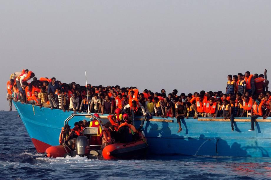 Um barco de resgate da organização espanhola Proactiva se aproxima de uma embarcação de madeira superlotada com imigrantes da Eritreia, ao largo da costa da Líbia no mar Mediterrâneo - 29/08/2016
