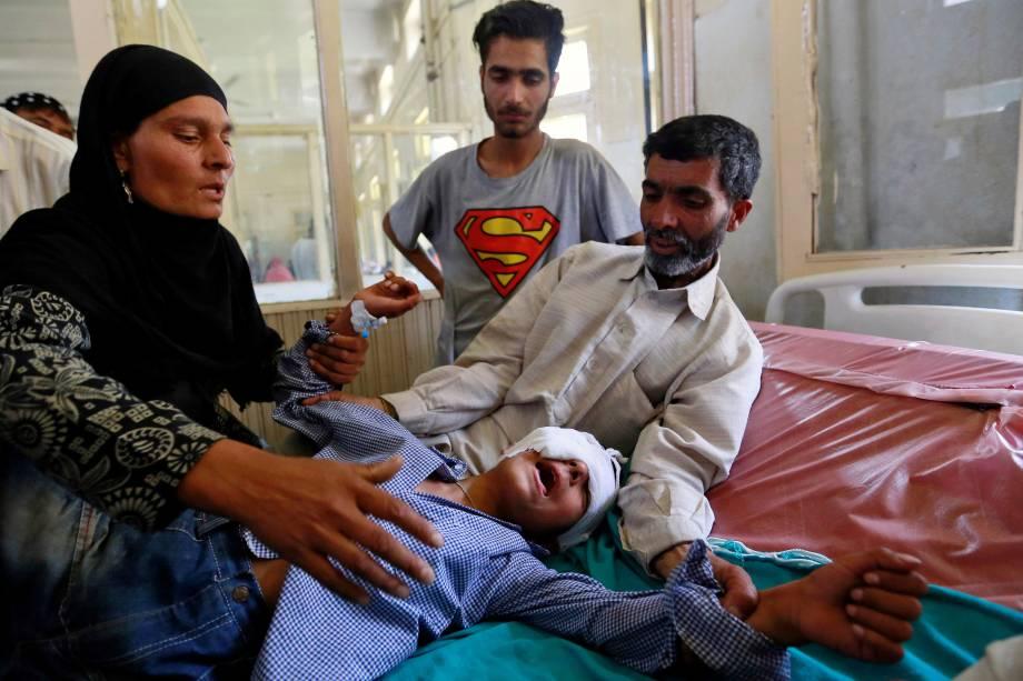 Os pais tentam confortar seu filho ferido durante confronto com forças de segurança em Srinagar durante onda de violência na região Caxemira, em Srinagar, na Índia - 18/06/2016