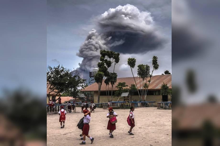 Estudantes brincam em uma escola enquanto o Monte Sinabung expele cinzas durante um erupção em Karo, província de Sumatra Setentrional, na Indonésia - 30/08/2016
