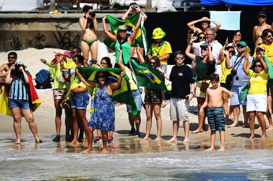 Torcedores levantam bandeiras e fotografam a prova de maratona aquática feminina, na beira da praia de Copacabana, Rio de Janeiro