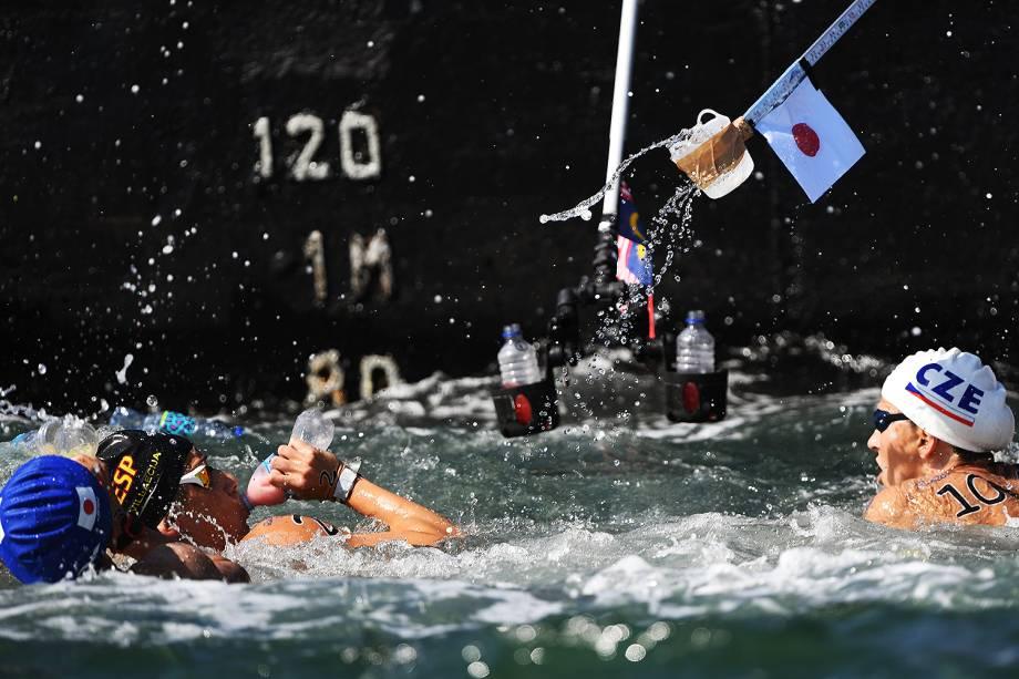 Pit-stops em barcos oferecem água mineral e isotônicos para as atletas que disputaram maratona aquática feminina na praia de Copacabana, no Rio de Janeiro