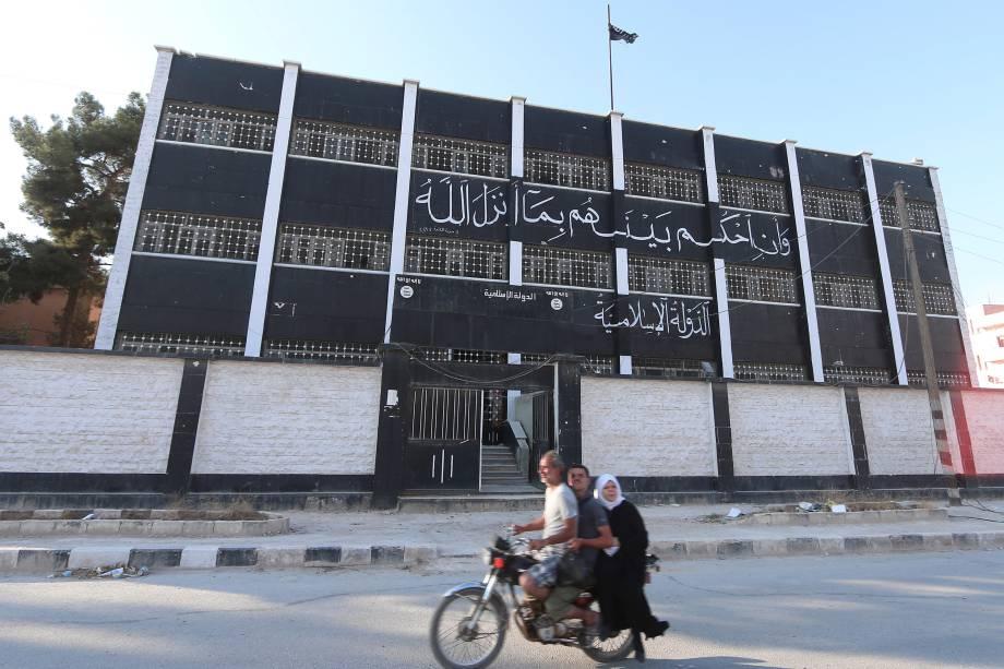 Civis passam em frente a um edifício usado como tribunal pelo Estado Islâmico na cidade retomada de Manbij, na Síria - 17/08/2016