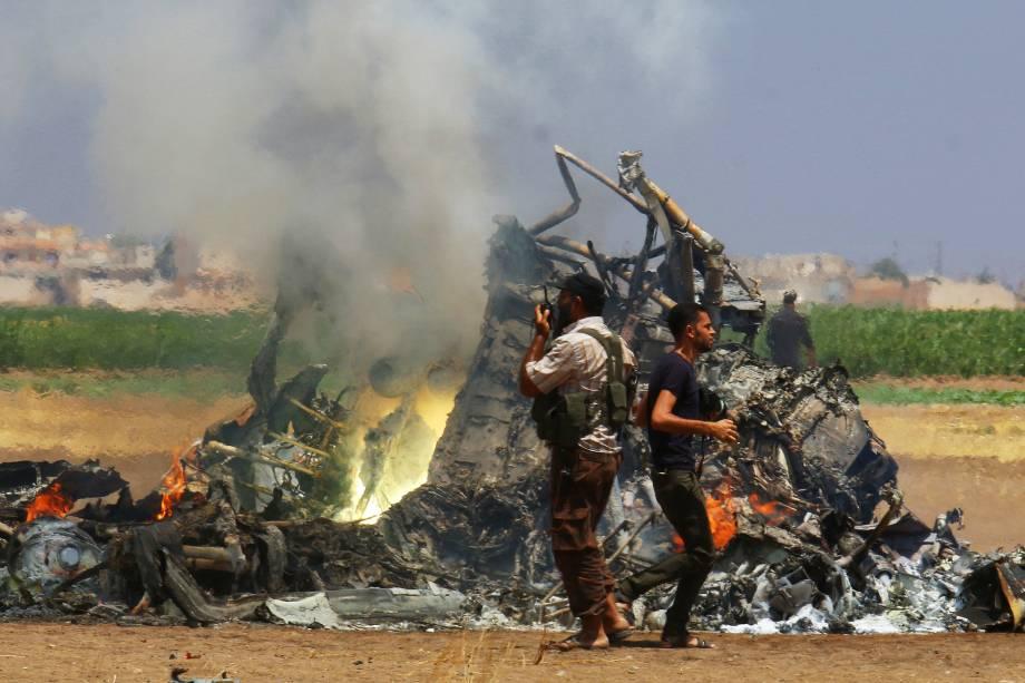 Homens inspecionam os destroços de um helicóptero russo derrubado na província síria de Idlib, controlada por rebeldes - 01/08/2016