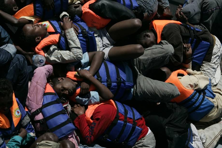 Imigrantes ilegais resgatados pela Marinha de Malta dormem no convés de uma embarcação militar