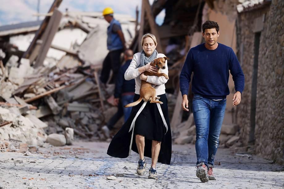 Mulher carrega cão nos braços em meio aos prédios destruídos na cidade italiana de Amatrice, após forte terremoto atingir a região - 24/08/2016