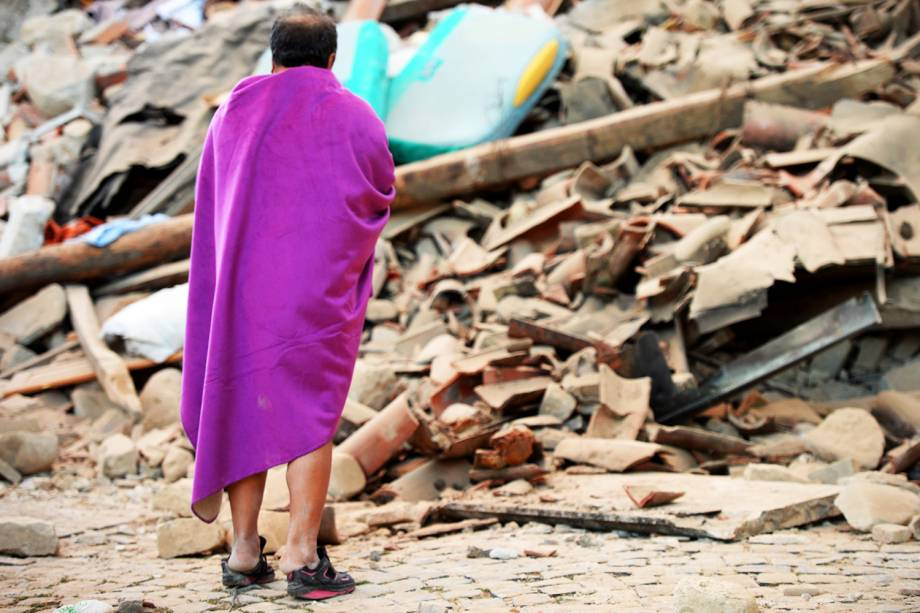 Homem caminha em meio aos escombros de uma casa, após forte terremoto atingir a região de Amatrice, na Itália - 24/08/2016