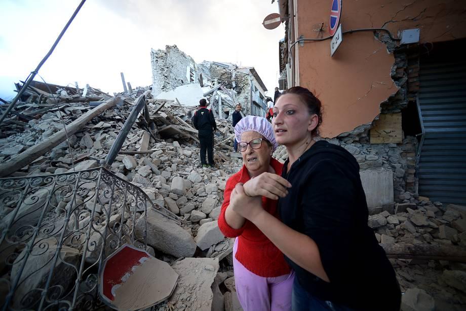 Moradores caminham entre escombros de prédios, após forte terremoto atingir a região de Amatrice, na Itália - 24/08/2016