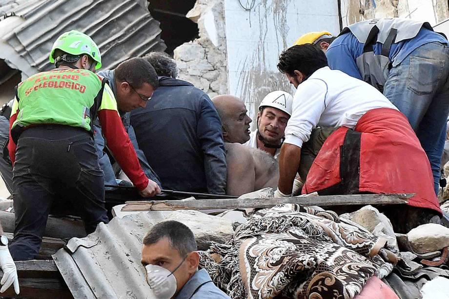 Sobrevivente é retirado de escombros, após um terremoto de magnitude 6.2 atingir a cidade de Amatrice, na Itália
