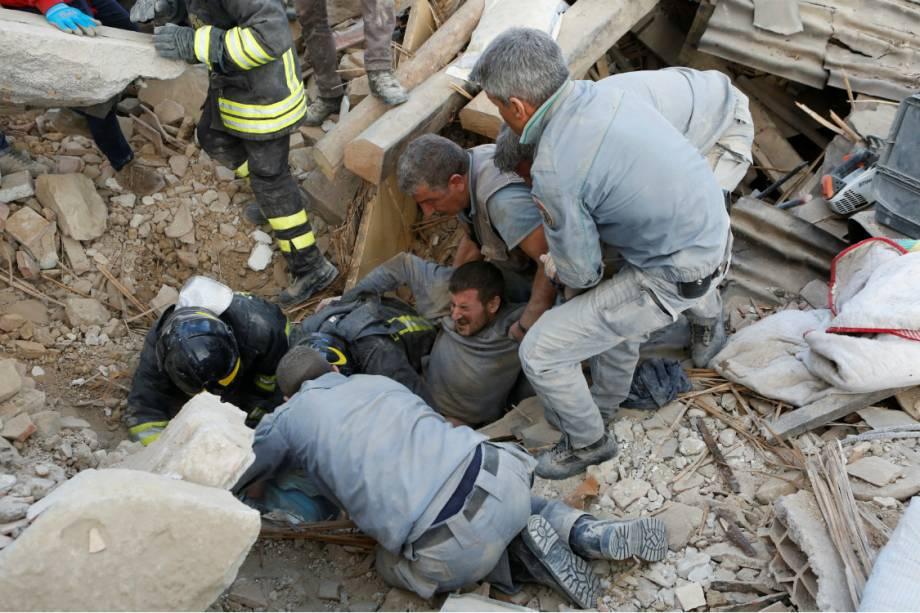 Bombeiros e civis resgatam um homem em Amatrice, na Itália, após forte terremoto atingir a região - 24/08/2016