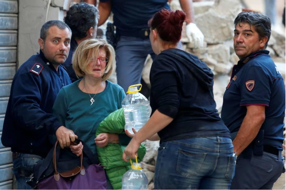 Socorristas auxiliam uma mulher resgatada em Amatrice, na Itália, após forte terremoto atingir a região - 24/08/2016