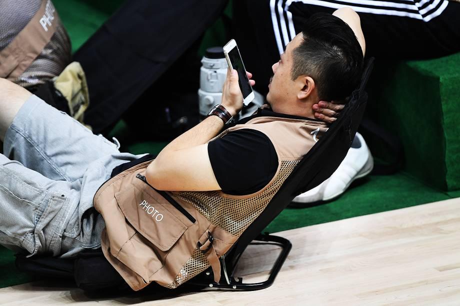 Fotógrafo descansa durante intervalo do jogo de basquete entre Estados Unidos e China