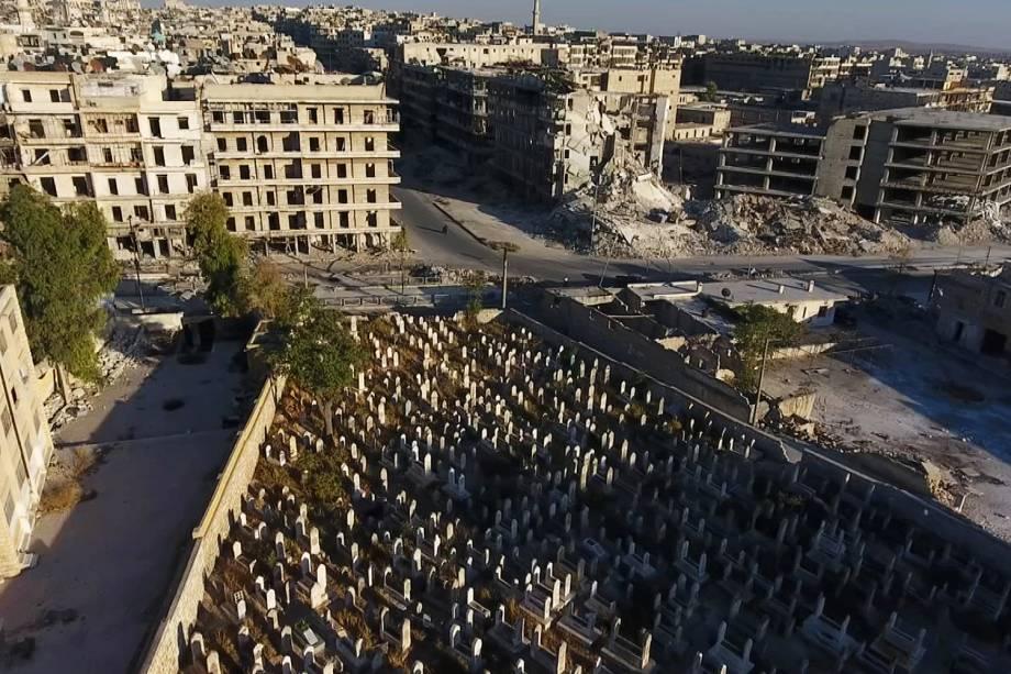 Imagem mostra um cemitério rodeado por prédios destruídos em uma área controlada por rebeldes na cidade de Alepo, na Síria - 27-09-2016