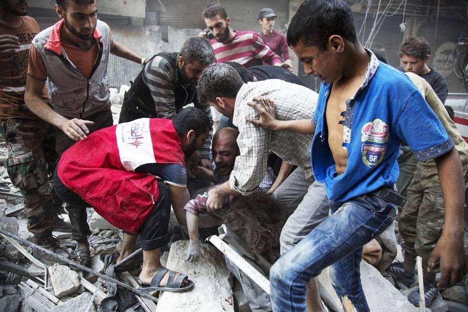 Um homem se desespera ao ver o corpo de sua filha do meio dos destroços de um prédio após um bombardeio no bairro de Al-Shaar em Alepo, na Síria - 27-09-2016
