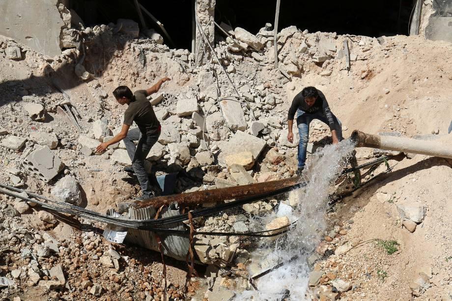 Homens inspecionam buraco no chão, resultado de um ataque aéreo na região de Alepo, na Síria