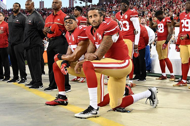 Colin Kaepernick (dir) e Eric Reid (esq), do San Francisco 49ers, ajoelham em forma de protesto durante a execução do hino nacional americano, antes de partida válida pela NFL - 12/09/2016