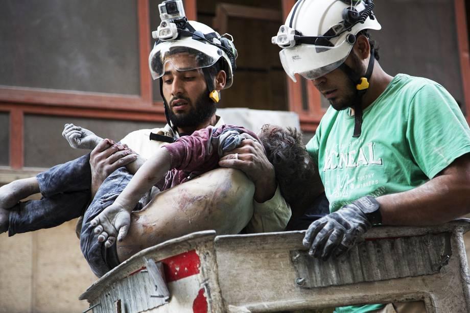 Bombeiros retiram o corpo de uma menina do meio dos destroços de um prédio, após um bombardeio no bairro de Al-Shaar em Alepo, na Síria - 27-09-2016